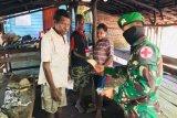 TNI lakukan penyemprotan disinfektan dan bagi masker warga kampung Rawa Biru Merauke