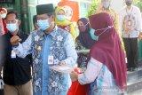 Gubernur Kalsel Sahbirin Noor (kiri) menyerahkan surat keterangan kepada pasien positif COVID-19 yang dinyatakan sembuh di RSUD Anshari Shaleh Banjarmasin, Kalimantan Selatan, Kamis (25/6/2020). Pemerintah Provinsi Kalimantan Selatan melepas kepulangan 45 pasien positif COVID-19 yang telah dinyatakan sembuh setelah menjalani perawatan. Foto Antaranews Kalsel/Bayu Pratama S.