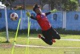 Penjaga gawang tim Arema FC, Kartika Aji berusaha menepis bola saat mengikuti latihan di lapangan Satsui Tubun, Malang, Jawa Timur, Kamis (25/6/2020). Latihan yang dilakukan di masa transisi normal baru tersebut hanya diikuti para pesepak bola yang berposisi sebagai penjaga gawang sementara pemain lainnya mengikuti latihan secara daring dari rumah. Antara Jatim/Ari Bowo Sucipto/zk.