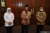 Menteri Koordinator bidang Politik, Hukum dan Keamanan Mahfud MD (tengah) didampingi Menteri Dalam Negeri Tito Karnavian (kanan) dan Gubernur Jawa Timur Khofifah Indar Parawansa (kiri) memberikan keterangan pers usai Rapat Koordinasi Kesiapan Pelaksanaan Pilkada Serentak Tahun 2020 di Surabaya, Jawa Timur, Jumat (26/6/2020). Rapat yang dihadiri perwakilan dari KPU Provinsi Jawa Timur, Bawaslu Jawa Timur dan sejumlah perwakilan kepala daerah kabupaten/kota tersebut membahas isu strategis dalam rangka memantapkan pelaksanaan Pilkada serentak tahun 2020 dengan penerapan secara ketat protokol kesehatan untuk mencegah penyebaran COVID-19. Antara Jatim/Moch Asim/zk.