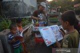 Sejumlah bocah membaca buku yang dibawa penjual pentol Lutfan Efendi di Desa Ngudirejo, Kecamatan Diwek, Kabupaten Jombang, Jawa Timur, Sabtu (27/6/2020). Lutfan Efendi membawa buku bacaan mulai dari pengetahuan, buku cerita dan buku bacaan lainnya guna menumbuhkan minat baca masyarakat terutama anak-anak sembari berjualan. Antara Jatim/Syaiful Arif/zk.
