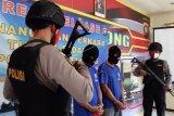 Dua tersangka kurir sabu dari Malaysia dihadirkan dalam rilis kasus di Mapolsek Entikong, Kabupaten Sanggau, Kalimantan Barat, Jumat (26/6/2020). Polsek Entikong menggagalkan penyelundupan empat paket sabu seberat 2,9 kilogram dari Malaysia yang dilakukan oleh dua tersangka kurir jaringan internasional berinisial RDM dan S melalui jalur tikus di kawasan perbatasan Entikong. ANTARA FOTO/Agus Alfian/jhw/pras.
