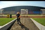 Petugas melakukan perawatan rutin di lapangan Stadion Gelora Sriwijaya Jakabaring Palembang, Sumatera Selatan, Minggu (28/6/2020). Stadion Gelora Sriwijaya Jakabaring Palembang menjadi salah satu dari enam stadion yang ditunjuk Persatuan Sepak Bola Seluruh Indonesia (PSSI) sebagai tuan rumah Piala Dunia U-20 Mei-Juni 2021 mendatang. ANTARA FOTO/Feny Selly/nym.