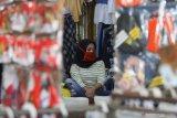 Karyawan memakai masker saat menjaga salah satu toko busana di Pasar Kapasan, Surabaya, Jawa Timur, Senin (29/6/2020). Pemerintah Provinsi Jawa Timur terus berupaya untuk menekan penyebaran COVID-19 diantaranya dengan menerapkan protokol kesehatan, membagikan masker secara gratis dan menggelorakan gerakan