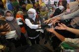 Gubernur Jawa Timur Khofifah Indar Parawansa (tengah) membagikan masker kepada pedagang dan pekerja di Pasar Kapasan, Surabaya, Jawa Timur, Senin (29/6/2020). Pembagian ribuan masker tersebut merupakan upaya mengedukasi masyarakat untuk bersama-sama mencegah penyebaran COVID-19 sekaligus menggelorakan gerakan