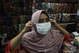 Pedagang memakai masker yang dibagikan secara gratis di Pasar Kapasan, Surabaya, Jawa Timur, Senin (29/6/2020). Pembagian ribuan masker tersebut merupakan upaya mengedukasi masyarakat untuk bersama-sama mencegah penyebaran COVID-19 sekaligus menggelorakan