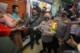 Kapolda Jawa Timur Irjen Pol M Fadil Imran (kedua kanan) membagikan masker kepada pedagang dan pekerja di Pasar Kapasan, Surabaya, Jawa Timur, Senin (29/6/2020). Pembagian ribuan masker tersebut merupakan upaya mengedukasi masyarakat untuk bersama-sama mencegah penyebaran COVID-19 sekaligus menggelorakan gerakan