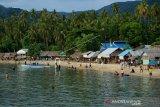Wisatawan mengujungi pantai Botutonuo di Kabupaten Bone Bolango. Salah satu obyek wisata favorit masyarakat Gorontalo tersebut kini mulai kembali ramai oleh pengunjung dan pedagang tapi masih sebagian besar masih mengabaikan protokol kesehatan seperti tidak mengenakan masker dan menjaga jarak. (ANTARA FOTO/Adiwinata Solihin)