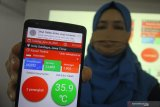 Salah satu perwakilan tim dari Universitas Dinamika (Undika) Pradita Maulidya Effendi memperlihatkan cara kerja aplikasi Dinamika New Normal (Dinno) di Surabaya, Jawa Timur, Selasa (30/6/2020). Aplikasi Dinno tersebut dapat mengingatkan pengguna agar selalu menjaga jarak saat berada dikerumunan dengan cara mengirimkan notifikasi memanfaatkan sinyal bluetooth. Antara Jatim/Moch Asim/zk.