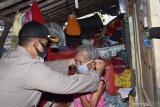 Kapolres Madiun Kota AKBP Bobby Aria Prakasa (kiri) memberikan masker kepada warga penerima bantuan bedah rumah saat bakti sosial penyerahan secara simbolis bantuan bedah rumah dalam rangka Hari Ulang Tahun (HUT) ke-74 Bhayangkara di Kota Madiun, Jawa Timur, Senin (29/6/2020). Dalam kegiatan bedah rumah warga tersebut Polres Madiun Kota bekerja sama dengan PT INKA (Persero). Antara Jatim/Siswowidodo/zk