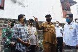 Wali Kota Madiun Maidi (ketiga kanan) dan Kapolres Madiun Kota AKBP Bobby Aria Prakasa (ketiga kiri) meninjau rumah warga penerima bantuan di sela-sela penyerahan secara simbolis bantuan bedah rumah dalam kegiatan bakti sosial HUT ke-74 Bhayangkara di Kota Madiun, Jawa Timur, Senin (29/6/2020). Dalam kegiatan bedah rumah warga tersebut Polres Madiun Kota bekerja sama dengan PT INKA (Persero). Antara Jatim/Siswowidodo/zk