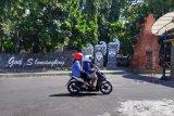 Pengendara berada di pintu gerbang area lokasi wisata Goa Selomangleng, Kota Kediri, Jawa Timur, Senin (29/6/2020). Pemerintah Kota Kediri belum membuka lokasi wisata, sebagai antisipasi mencegah penyebaran pandemi COVID-19. Antara Jatim/ Asmaul Chusna