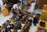 Pekerja mengemas produk sepatu kulit kualitas ekspor sebelum dikirim ke Malaysia dan Singapura di rumah produksi Shoeka Shoes di Malang, Jawa Timur, Selasa (30/6/2020). Pengusaha sepatu kulit ekspor setempat mengaku mengandalkan pemasaran digital serta berinovasi membuat produk baru yang murah dan disukai konsumen untuk mengatasi anjloknya permintaan dari seribu pasang menjadi enam ratus pasang per bulan atau menurun 40 persen akibat pandemi COVID-19. Antara Jatim/Ari Bowo Sucipto/zk.