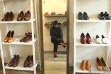 Calon pembeli mencoba mengenakan sepatu kulit kualitas ekspor yang dipajang di rumah produksi Shoeka Shoes di Malang, Jawa Timur, Selasa (30/6/2020). Pengusaha sepatu kulit ekspor setempat mengaku mengandalkan pemasaran digital serta berinovasi membuat produk baru yang murah dan disukai konsumen untuk mengatasi anjloknya permintaan dari seribu pasang menjadi enam ratus pasang per bulan atau menurun 40 persen akibat pandemi COVID-19. Antara Jatim/Ari Bowo Sucipto/zk.
