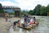 Sejumlah warga menggunakan jasa rakit saat menyeberangi sungai Bone, Bone Bolango, akibat jembatan Molintogupo yang rusak diterjang banjir bandang di Desa Alale, Kabupaten Bone Bolango, Gorontalo, Kamis (2/7/2020). Pembangunan penggantian jembatan Molintogupo yang menghubungkan Suwawa Selatan dan Suwawa Tengah tersebut mulai dikerjakan oleh Dinas PUPR dengan nilai kontrak Rp17,3 miliar. (ANTARA FOTO/Adiwinata Solihin)