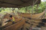 Pekerja menyelesaikan pembuatan perahu tradisional di Desa Pagirikan, Kecamatan Pasekan, Indramayu, Jawa Barat, Jumat (3/7/2020). Desa Pagirikan diberi julukan sebagai kampung perahu karena sekitar 70 persen warganya berprofesi sebagai pembuat perahu tradisional. ANTARA JABAR/Dedhez Anggara/agr