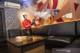 Petugas menyemprotkan cairan disinfektan di ruang karaoke saat simulasi pembukaan dan peninjauan tempat hiburan di F3X Executive Club, Bandung, Jawa Barat, Jumat (3/7/2020). Simulasi tersebut dilakukan dalam rangka peninjauan kesiapan tempat hiburan malam dalam penerapan protokol kesehatan seperti rapid test pengunjung, alat pelindung wajah bagi karyawan, masker, sarung tangan, jaga jarak dan cairan disinfektan seiring tatanan normal baru di tengah pandemi COVID-19. ANTARA JABAR/M Agung Rajasa/agr