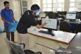 Petugas menggunakan cairan disinfektan membersihkan peralatan komputer di ruangan  peserta Ujian Tulis Berbasis Komputer Seleksi Bersama Masuk perguruan Tinggi Negeri (UTBK-SBMPTN) di Universitas Syiah Kuala (Unsyiah), Banda Aceh, Aceh, Sabtu (4/7/2020). Menjelang pelaksanaan UTBK-SBMPTN yang diikuti sebanyak 8.629 peserta pada Minggu (5/7/2020), pihak Universitas Syiah Kuala menerapkan protokol kesehatan guna mencegah penyebaran COVID-19. Antara Aceh/Ampelsa.