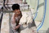Pekerja mengumpulkan endapan tepung sagu saat proses pengeringan di salah satu tempat pengolahan di Desa Pasi Aceh Tunong, Meureubo, Aceh Barat, Aceh, Sabtu (4/7/2020). Pelaku usaha mengatakan sejak sepekan terakhir permintaan tepung sagu yang dijual Rp2100 per kilogram tersebut kembali meningkat dari 25 ton menjadi 35 ton per sekali panen setelah sebelumnya sempat terhenti akibat pandemi COVID-19. Antara Aceh/Syifa Yulinnas.