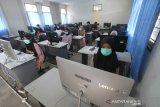 Sejumlah peserta menggunakan masker mengikuti Ujian Tertulis Berbasis Komputer (UTBK)  di Fakultas Teknik Universitas Lambung Mangkurat Banjarmasin, Kalimantan Selatan, Minggu (5/7/2020). Universitas Lambung Mangkurat mengadakan UTBK yang merupakan tahapan yang harus dilalui calon mahasiswa untuk melihat kemampuan sebelum mengikuti Seleksi Bersama Masuk Perguruan Tinggi Negeri (SBMPTN) 2020 dengan menerapkan protokol kesehatan secara ketat untuk mencegah penyebaran pandemi COVID-19. Foto Antaranews Kalsel/Bayu Pratama S.