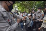 Polisi membubarkan paksa pengunjuk rasa dari Aliansi Mahasiswa Papua saat menggelar aksi di Denpasar, Bali, Senin (6/7/2020). Unjuk rasa yang rencananya digelar di dekat Kantor Agen Konsulat Amerika Serikat di Denpasar tersebut terpaksa dibubarkan karena tidak memiliki izin. ANTARA FOTO/Nyoman Hendra Wibowo/nym.