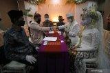 Pasangan pengantin melaksanakan prosesi akad nikah saat simulasi resepsi pernikahan di masa normal baru di Hotel Royal Singosari Cendana, Surabaya, Jawa Timur, Senin (6/7/2020). Kegiatan simulasi resepsi pernikahan tersebut bertujuan untuk mengedukasi masyarakat tentang pentingnya penerapan protokol kesehatan dalam acara pernikahan guna mencegah penyebaran dan penularan COVID-19 di masa normal baru. Antara Jatim/Moch Asim/zk.