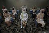 Calon pengantin perempuan duduk berjarak dengan keluarganya saat simulasi resepsi pernikahan di masa normal baru di Hotel Royal Singosari Cendana, Surabaya, Jawa Timur, Senin (6/7/2020). Kegiatan simulasi resepsi pernikahan tersebut bertujuan untuk mengedukasi masyarakat tentang pentingnya penerapan protokol kesehatan dalam acara pernikahan guna mencegah penyebaran dan penularan COVID-19 di masa normal baru. Antara Jatim/Moch Asim/zk.