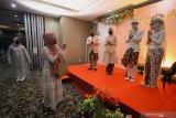 Tamu undangan memberikan ucapan selamat kepada pasangan pengantin beserta keluarganya saat simulasi resepsi pernikahan di masa normal baru di Hotel Royal Singosari Cendana, Surabaya, Jawa Timur, Senin (6/7/2020). Kegiatan simulasi resepsi pernikahan tersebut bertujuan untuk mengedukasi masyarakat tentang pentingnya penerapan protokol kesehatan dalam acara pernikahan guna mencegah penyebaran dan penularan COVID-19 di masa normal baru. Antara Jatim/Moch Asim/zk.