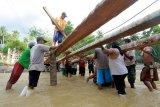 Sejumlah warga bergotong rotong membangun jembatan darurat di Desa Tulabolo, Kabupaten Bone Bolango, Gorontalo, Minggu (5/7/2020). Jembatan yang terbuat dari kayu kelapa tersebut dibangun agar akses kecamatan Suwawa dan Kecamatan Pinogu kembali terhubung pascabanjir yang menghanyutkan jembatan utama pada Jumat (3/7). ANTARA FOTO/Adiwinata Solihin/aww.