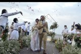 Sejumlah tamu undangan menyambut pasangan pengantin saat simulasi penyelenggaraan kegiatan pernikahan di kawasan Nusa Dua, Badung, Bali, Senin (6/7/2020). Simulasi yang diselenggarakan Bali Wedding Association tersebut sebagai upaya sosialisasi dan pedoman penyelenggaraan pernikahan yang menerapkan protokol kesehatan pencegahan COVID-19 secara ketat selama masa normal baru. ANTARA FOTO/Fikri Yusuf/nym.