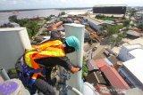 Teknisi melakukan pemeliharaan perangkat Base Transceiver Station (BTS) milik XL Axiata di Banjarmasin, Kalimantan Selatan, Selasa (7/7/2020). XL Axiata siap memasuki era normal baru (new normal), termasuk menyediakan jaringan data yang memadai untuk melayani sekitar satu juta pelanggan di seluruh Kalimantan Selatan. Berdasarkan trafik data XL Axiata saat ini telah kembali melandai setelah sempat meningkat secara rata-rata hingga 15 persen dibandingkan hari normal sebelum ada pandemi Covid-19. Foto Antaranews Kalsel/Bayu Pratama S.
