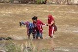 Sejumlah warga melintasi sungai di Desa Tulabolo, Kabupaten Bone Bolango, Gorontalo. Warga terpaksa harus melintasi sungai karena jembatan yang menjadi akses utama hanyut terbawa arus banjir pada Jumat (3/7) lalu. (ANTARA FOTO/Adiwinata Solihin)