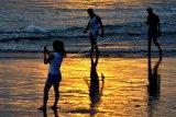 Wisatawan mengunjungi kawasan Pantai Kuta, Badung, Bali, Kamis (9/7/2020). Pengelola Pantai Kuta mulai membuka kembali kawasan yang merupakan salah satu destinasi pariwisata utama di Pulau Dewata tersebut setelah sebelumnya sempat ditutup selama lebih dari tiga bulan sebagai upaya pencegahan penyebaran pandemi COVID-19. ANTARA FOTO/Fikri Yusuf/nym.