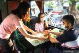Pramusaji menyajikan minuman di dalam bus pariwisata yang dialih fungsikan menjadi cafe wisata berjalan dengan nama  Ngopi Uklam 87 di Malang, Jawa Timur, Jumat (10/7/2020). Cafe wisata berjalan tersebut dioperasikan sebagai upaya kreatif pengusaha bus pariwisata agar armadanya tetap beroperasi sekaligus membangkitkan sektor pariwisata yang belum sepenuhnya pulih akibat pandemi COVID-19. Antara Jatim/Ari Bowo Sucipto/zk.