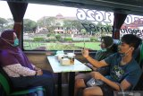 Wisatawan memotret rekannya di bus pariwisata yang dialih fungsikan menjadi cafe wisata berjalan dengan nama  Ngopi Uklam 87 di Malang, Jawa Timur, Jumat (10/7/2020).  Cafe wisata berjalan tersebut dioperasikan sebagai upaya kreatif pengusaha bus pariwisata agar armadanya tetap beroperasi sekaligus membangkitkan sektor pariwisata yang belum sepenuhnya pulih akibat pandemi COVID-19. Antara Jatim/Ari Bowo Sucipto/zk.