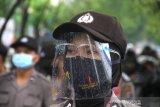 Polisi wanita menggunakan pelindung wajah serta masker saat bersiaga di depan DPRD Provinsi Kalsel ketika berlangsung aksi unjuk rasa di Jalan Lambung Mangkurat Banjarmasin, Kalimantan Selatan, Jumat (10/7/2020). Para pengunjuk rasa menolak Rancangan Undang-Undang Haluan Ideologi Pancasila (RUU HIP) karena dinilai mengandung unsur komunisme dan berharap pemerintah mencabut RUU HIP dari program legislasi nasional (Prolegnas) 2020. Foto Antaranews Kalsel/Bayu Pratama S.