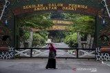 Warga melintas di depan gerbang utama Markas Besar  Secapa TNI AD di Hegarmanah, Bandung, Jawa Barat, Jumat (10/7/2020).  Pihak TNI AD melalui Kepala Staf Angkatan Darat direncanakan akan memberi keterangan resmi pada Sabtu (11/7) terkait data Gugus Tugas Percepatan Penanganan COVID-19 yang melansir sekitar 1200 kasus positif COVID-19 di Secapa TNI AD dengan 17 orang masih menjalani perawatan di rumah sakit. ANTARA JABAR/Novrian Arbi/agr