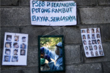 Tukang potong rambut, Suyadi, menggunakan Alat Pelindung Diri (APD) saat melayani pelanggan di kawasan Siwalankerto, Surabaya, Jawa Timur, Rabu (13/5/2020). Sepinya pengunjung yang datang ke
