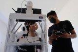 Mahasiswa memeriksa tekanan darah dengan menggunakan robot rakitan saat melakukan uji coba di ruang Unit Kegiatan Mahasiswa (UKM) Robotec Universitas Udayana, Denpasar, Bali, Jumat (10/7/2020). Robot hasil karya mahasiswa Teknik Elektro dan Teknik Mesin tersebut dilengkapi alat untuk memeriksa tekanan darah, suhu tubuh dan tempat pengiriman makanan maupun obat-obatan bagi pasien sehingga ditargetkan dapat membantu tugas tenaga medis yang berisiko tinggi dalam menangani penderita COVID-19. ANTARA FOTO/Nyoman Hendra Wibowo/nym.