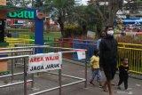 Pengunjung berjalan-jalan di ruang wisata publik yang baru dibuka setelah lebih dari dua bulan ditutup untuk umum di Alun-alun Batu, Jawa Timur, Sabtu (11/7/2020). Selain menerapkan protokol kesehatan yang ketat, pengelola ruang wisata publik tersebut juga membatasi jumlah pengunjung serta mengurangi batas waktu kunjungan guna mencegah penyebaran COVID-19. Antara Jatim/Ari Bowo Sucipto/zk.
