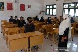 Guru memberikan arahan kepada murid baru dalam ruangan kelas dengan pembatasan jaga jarak saat simulasi penerapan protokol kesehatan di SMA-1 Banda Aceh, Aceh, Sabtu (11/7/2020). Sebagian SMA/SMK di daerah itu menyatakan siap memulai Proses Belajar Mengajar (PBM) tahun ajaran baru 2020/2021 yang dijadwalkan pada, Senin (13/7/2020), baik secara tatap muka maupun daring dengan penerapan prorokol kesehatan guna mencegah penyebaran COVID-19, namun hingga saat ini pihak sekolah masih menunggu keputusan dari pemerintah. Antara Aceh/Ampelsa.