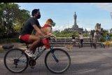 Pesepeda membawa anjing peliharaannya yang menggunakan masker dalam uji coba hari bebas kendaraan di kawasan Lapangan Puputan Margarana Denpasar, Bali, Minggu (12/7/2020). Pemerintah Kota Denpasar melakukan uji coba hari bebas kendaraan dengan pembatasan waktu yaitu 06.00 - 08.00 Wita dan penerapan protokol kesehatan normal baru tahap I serta akan dievaluasi baik buruknya terkait penularan COVID-19. ANTARA FOTO/Nyoman Hendra Wibowo/nym.