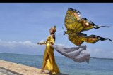 Model memperagakan busana bernuansa layang-layang disela-sela kegiatan Lomba Layangan Virtual di Sanur, Denpasar, Bali, Minggu (12/7/2020). Kegiatan yang diikuti 380 peserta dari berbagai daerah seperti Bali, NTB dan Sulawesi Utara tersebut dilakukan dengan proses penerbangan layangan yang dilakukan dari lingkungan tempat tinggal peserta dan ditampilkan serta dinilai melalui aplikasi 'Zoom' yang diselenggarakan untuk mewadahi pehobi layang-layang agar tetap dapat berkompetisi selama masa pandemi COVID-19. ANTARA FOTO/Fikri Yusuf/nym.