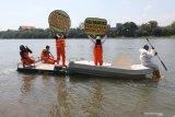 Aktivis lingkungan hidup dari Ecological Observation and Wetlands Conservation (Ecoton) membentangkan poster saat aksi tolak pencemaran sungai Brantas di Kota Kediri, Jawa Timur, Minggu (12/7/2020). Tim peneliti Ecoton menemukan sejumlah polutan berbahaya di sungai terpanjang ke dua di pulau Jawa tersebut yakni di antaranya kandungan mikroplastik yang dapat merusak ekosistem dan berbahaya bagi kesehatan manusia. Antara Jatim/Prasetia Fauzani/zk