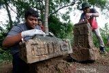 Warga bersama aktivis peduli sejarah yang tergabung dalam Masyarakat Peduli Sejarah Aceh (MAPESA) membersihkan dan menata ulang batu nisan peninggalan abad 14 hingga 18 Masehi di Desa Lampaloh, Banda Aceh, Aceh, Minggu (12/7/2020). Pembersihan dan perawatan nisan kuburan kuno dilakukan aktivis MAPESA sebagai upaya menjaga dan melestarikan peninggalan bersejarah. Antara Aceh/Irwansyah Putra.