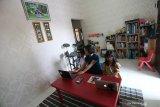 Orangtua murid membantu anaknya yang merupakan peserta didik baru tingkat Sekolah Dasar (SD) dan Taman Kanak-kanak mengoperasikan perangkat komputer jinjing, saat mengikuti Masa Pengenalan Lingkungan Sekolah (MPLS) secara daring di Blitar, Jawa Timur, Senin (13/7/2020). Memasuki masa hari pertama sekolah tahun ajaran baru 2020 ini, Kemendikbud RI masih hanya memberikan ijin pemberlakuan masuk sekolah secara tatap muka terhadap 104 kabupaten/kota di seluruh indonesia yang termasuk zona hijau dalam peta penyebaran COVID-19, sedangkan bagi kabupaten/kota lainnya yang masih termasuk dalam zona kuning dan merah, masih harus memberlakukan pembelajaran melalui sistem daring dari rumah. Antara Jatim/Irfan Anshori/zk