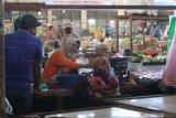 Pedagang bertransaksi tanpa menggunakan masker dengan baik di pasar Pahing yang baru saja dibuka di Kota Kediri, Jawa Timur, Senin (13/7/2020). Pemerintah daerah setempat membuka kembali pasar tradisional itu setelah sebelumnya ditutup selama tiga hari pasca seorang pedagang dinyatakan positif COVID-19. Antara Jatim/Prasetia Fauzani/zk