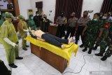 Petugas dari RS Bhayangkara Kediri memberi contoh cara pemulasaran jenazah COVID-19 di Polresta Kediri, Jawa Timur, Senin (13/7/2020). Pelatihan pemulasaran jenazah yang diikuti oleh Bhayangkara Pembina Keamanan dan Ketertiban Masyarakat (Bhabinkamtibmas), Bintara Pembina Desa (Babinsa), perangkat desa, dan relawan tersebut guna mewujudkan kampung tangguh menghadapai pandemi COVID-19. Antara Jatim/Prasetia Fauzani/zk.