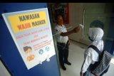 Petugas memeriksa suhu tubuh siswi sebelum masuk ke sekolah di SMAN 1 Slawi, Kabupaten Tegal, Jawa Tengah, Selasa (14/7/2020). Menurut pihak sekolah melalui surat edaran dari Dinas Pendidikan Jawa Tengah mulai 14 Juli hingga 15 Juli kegiatan Masa Pengenalan Lingkungan Sekolah (MPLS) siswa baru SMA/SMK dihentikan dan digantikan MPLS secara daring akibat masih tingginya penularan dan penyebaran COVID-19 di Jawa Tengah. ANTARA FOTO/Oky Lukmansyah/nym.