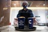 Adaptasi kebiasaan baru di bioskop, pembeli popcorn disajikan dengan nampan